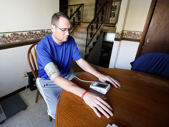 Rick Gilgenbach Jr. takes his blood pressure in his Fond du Lac house Monday, three weeks after receiving a transplanted heart. November 6, 2017. Doug Raflik/USA TODAY NETWORK-Wisconsin