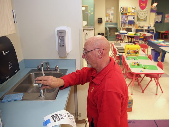 Bremerton School District plumber Rick Powell checks the new faucet he installed to see if the water is running properly at Crownhill Elementary School in Bremerton.