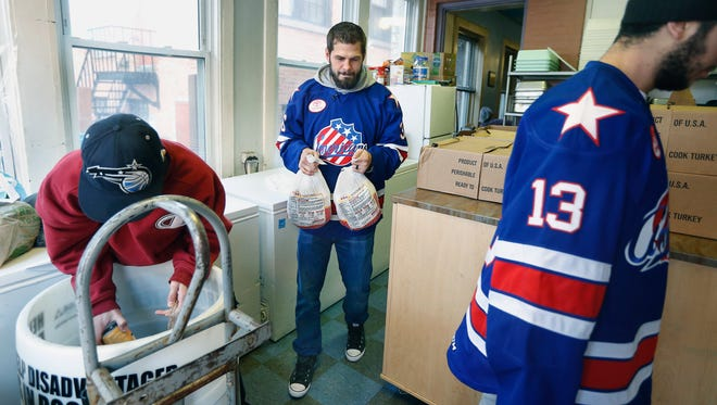 AThe Amerks' Patrick Kaleta helps deliver 28 turkeys to the Open Door Mission. Joseph Rivera, front, and Nick Baptiste help.