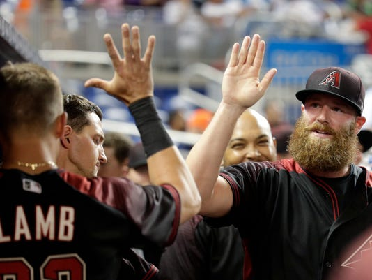 Arizona Diamondbacks relief pitcher Archie Bradley, right, is high-fived in the dugout after pitching a scoreless eighth inning during the team's baseball game against the Miami Marlins, Thursday, June 1, 2017, in Miami. The Diamondbacks won 3-2. (AP Photo/Lynne Sladky)