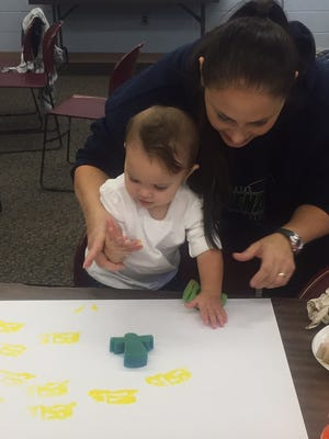 Tina Mingin and her daughter Tia enjoy painting with shapes during a Li'l Listeners 1000 Books Before Kindergarten program at Cumberland County Library in Bridgeton.