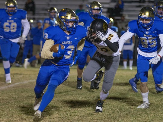 Reed's Champ Robertson runs away from Galena's Josh Kiley in the second half of their playoff football game on Nov. 9