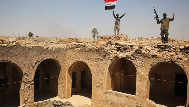 Fighters backing Iraqi forces pose with the Iraqi flag from Tal Afar's Ottoman-era historic citadel after troops took control of the area from the Islamic State on Aug. 27, 2017.
