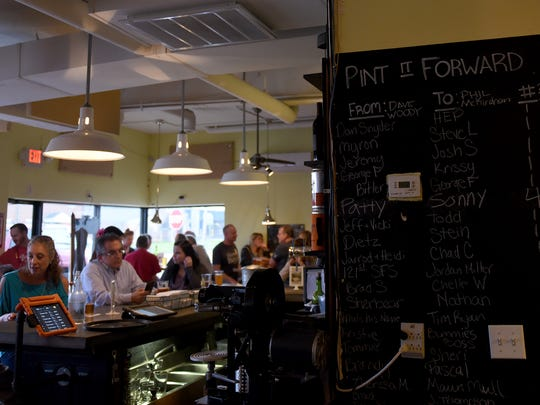 """The """"Pint It Forward"""" chalkboard at Buckeye Lake Brewery. Patrons will buy drinks for friends through the note system at the local brewery."""