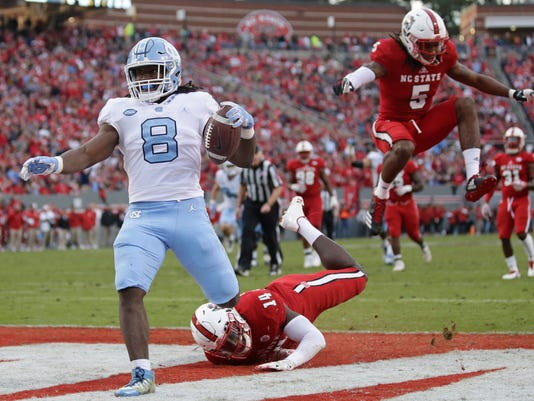 North Carolina running back Michael Carter (8) scores as North Carolina State safety Dexter Wright (14) and cornerback Johnathan Alston (5) chase during the first half of an NCAA college football game in Raleigh, N.C., Saturday, Nov. 25, 2017. (AP Photo/Gerry Broome)