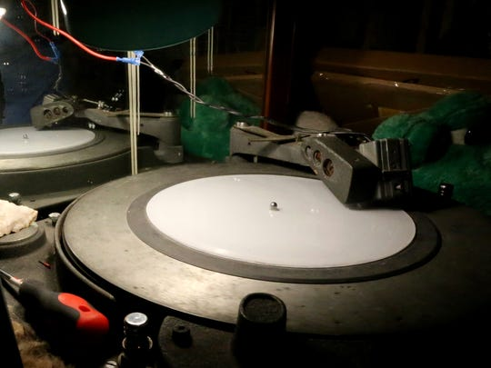 The grooves in the vinyl record are cut into the material using a magnetic cutting head during the lathe cutting process.