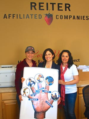 Three women who work in the Sembrando Salud farmworker health program at Reiter Affiliated Companies hold a sign in Spanish that lists five steps to healthy living. They are Gabby Guzman, left, program coordinator; Priscila Cisneros, program manager; and Martha Ortega, educator.