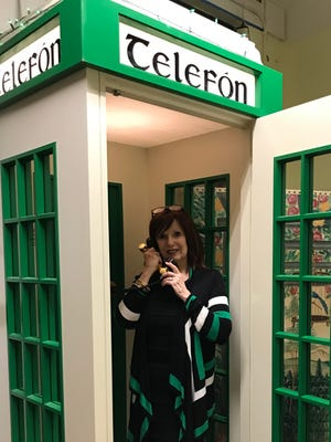 Maureen A. Kennedy in telephone booth from South Dublin Balleyfermot. Shamus Roche donated the booth to the Irish Heritage Center.