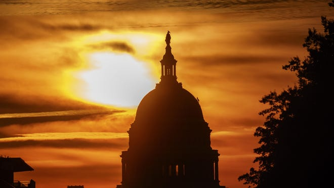 FILE- In this Oct. 26, 2018, file photo the rising sun silhouettes the U.S. Capitol dome at daybreak in Washington. A new government report says that the U.S. budget deficit is set to hit $897 billion this year and predicts that economic growth will slow as the effects of President Donald Trump's tax cut on business investment begin to drop off. (AP Photo/Alex Brandon, File)