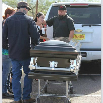 Josh Barela (left) stands by the casket carrying his