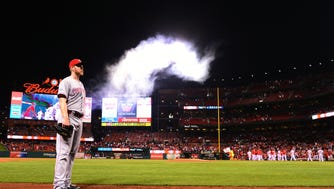 Reds relief pitcher Blake Wood looks on as the Cardinals celebrate their walk-off win.