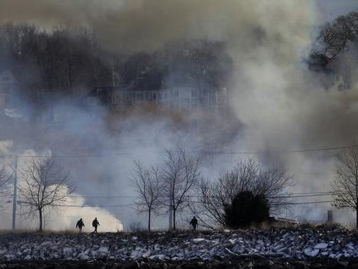 First responders work through the smoke and the fire at the shooting scene on Lake Road in Webster on Christmas Eve.