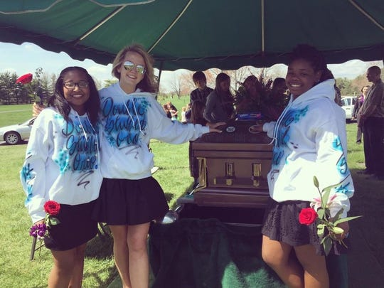 """Wyche, Hausfeld, and Thomas wearing the """"Double-Stuffed Oreo"""" sweatshirt with Crow's casket at her funeral."""