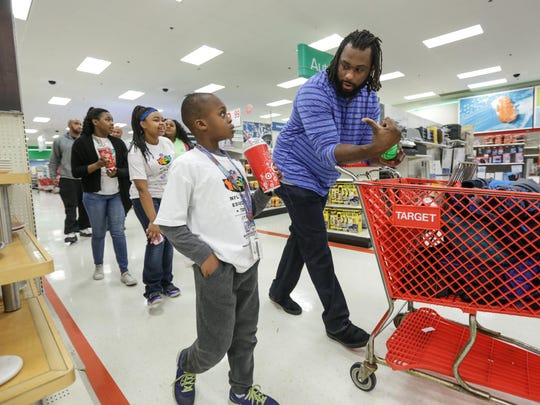 Brandon Pettigrew talks with Elijah Eigbokhan, 7, of the Dick & Sandy Dauch Home of the NFL/ YET Boys & Girls Club while giving Eigbokhan and five others $300 each to spend due to having good grades and behavior at Target in Dearborn on Tuesday.