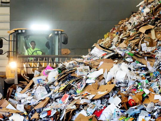 A bulldozer moves piles of recyclables toward a conveyor,