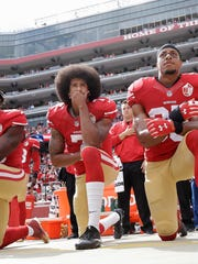 In this Oct. 2, 2016, file photo, from left, San Francisco 49ers outside linebacker Eli Harold, quarterback Colin Kaepernick and safety Eric Reid kneel during the national anthem before an NFL football game against the Dallas Cowboys in Santa Clara, Calif.