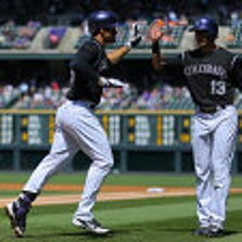 DENVER, CO - AUGUST 24: Nolan Arenado #28 of the Colorado Rockies is congratulated by Drew Stubbs #13 after his two run home run during the first inning against the Miami Marlins at Coors Field on August 24, 2014 in Denver, Colorado. (Photo by Justin Edmonds/Getty Images)