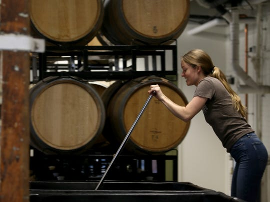 Colleen Hardy punching down the cap on Cabernet Franc from east side of Seneca Lake in the winery at Living Roots in Rochester.