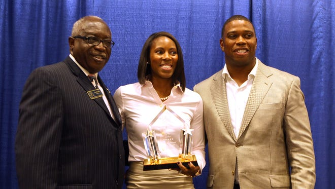 Ben Harris, left, chair of the Minority Enterprise Development Week Committee, presents Kimberly and Angelo Crowell with the annual Reginald L. Rolle Economic Development Champion of the Year award during the MED Week luncheon Thursday. The Crowells own Kalo Restaurant Group LLC, the area franchisee for Jersey Mike's Subs.