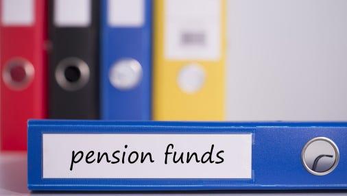 Pension funds on blue business binder.