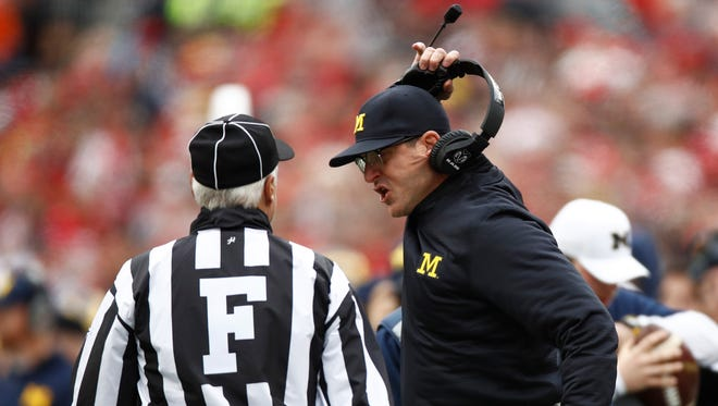 Jim Harbaugh removes his headset while arguing a call Saturday against Ohio State.