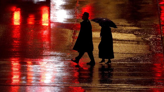 In this Dec. 26, 2018 file photo, pedestrians are silhouetted against wet pavement as they walk in the Country Club Plaza shopping district in Kansas City, Mo.