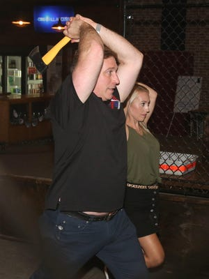 John Eslich, owner of All American Axe Throwing, shows the proper form. Also visible in the background is Allyson Eslich.