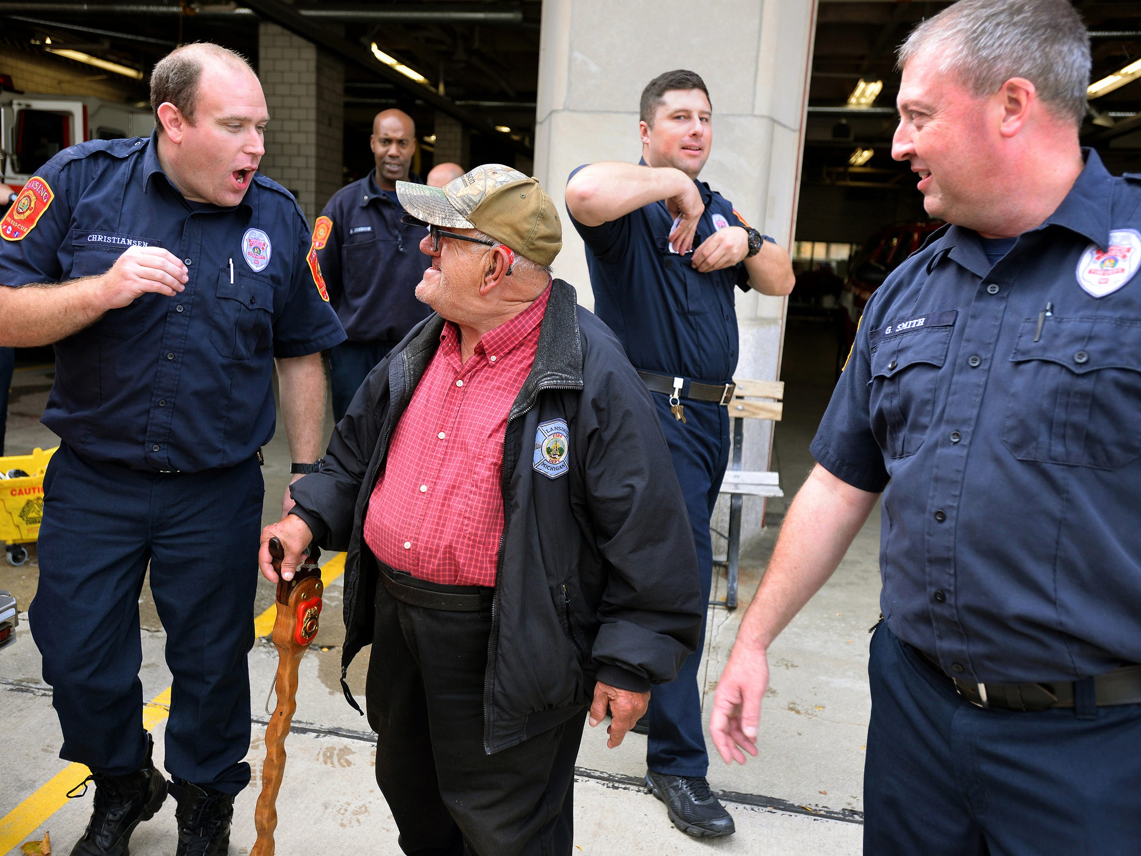 Tony Tumminello, 75, hangs out with the firefighters at Lansing's Fire Station One including Bill Christiansen, left, and Greg Smith, right, recently.
