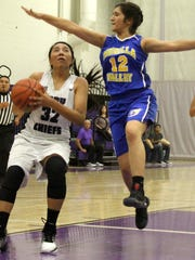 Mescalero's Katelyn Yuzos, left, drives toward the basket while being defended by Mesilla Valley's Lauren Sanchez.