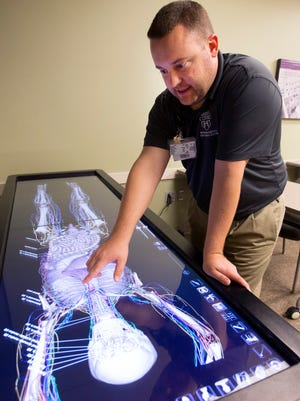 Todd Tripoli, a simulation technologist, shows off an Anatomage Table used to teach and plan for patient care at Mayo Clino. The hospital received a five-star rating in a recent survey of patients.