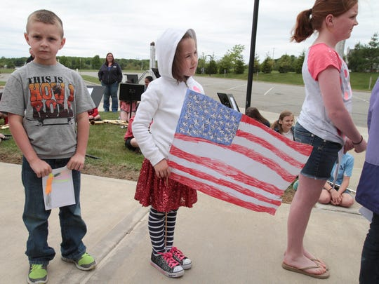 Pictured (from left to right): Nicholas Lang, 6, Lucy Wegener, 6, and Abigail Thornton, 11, stand in line to present a gift to the veterans of Post 1776 during the flag raising ceremony in observance of Memorial Day at Benedict A. Cucinella Elementary School in Long Valley in Washington Township on May 21, 2015.