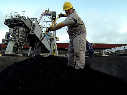 Jason Benac of Sault Ste. Marie moves coal around in a cargo hold full of it so the lid can be safely placed on it and locked down for the long trip.