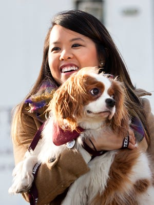 Nina Pham holds up her dog, Bentley, at Hensley Field in Grand Prairie, Texas, Nov. 1, 2014. Pham, who recovered from Ebola, and the King Charles Spaniel were reunited privately on Saturday in a vacant residence.decommissioned naval air base, where he was quarantined for 21 days.