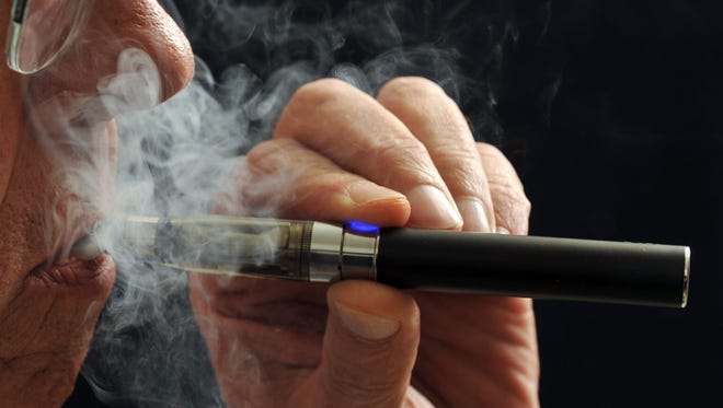 In this photo illustration, a smoker puffs on an e-cigarette.