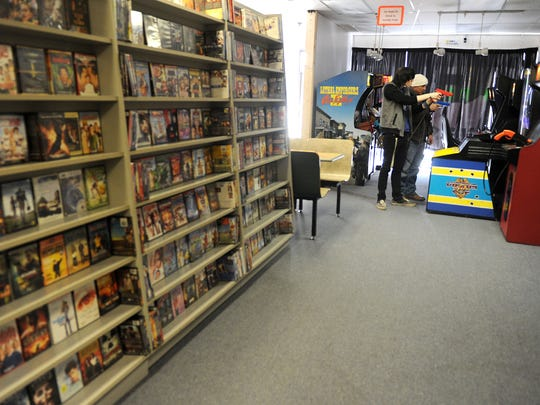 Shelves of movies and video games for sale fill the space behind the arcade area at Geeksters where Jaden and Mathew Hall play Virtua Cop Tuesday afternoon. Geeksters hours are 11 a.m. to 7 p.m. Tuesday through Saturday.