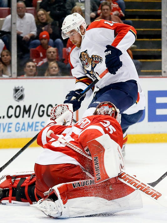 Detroit Red Wings goalie Jimmy Howard (35) stops a Florida Panthers right wing Jimmy Hayes (12) shot in the first period of an NHL hockey game in Detroit Friday, Dec. 12, 2014. (AP Photo/Paul Sancya)