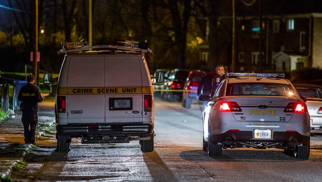A crime lab van and an IMPD car idle in the 3500 block of Evergreen Avenue where a man was fatally shot March 29.