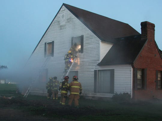 Stayton firefighting crews practice rescuing a firefighter during a drill taking place at a house on Gardner Ave. The house is owned by North Santiam School District and is being demolished to expand the sports fields.