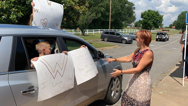 Township 3 Elementary School Principal Molly Blanton laughs at one of the signs a student made for her retirement parade.