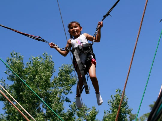 Miyana Denarend flies high above the air on a bungee trampoline harness on, July 4, 2016, during the Freedom Days' Party in the Park at Brookside Park in Farmington.