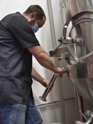 "Ben Wade, co-owner of Albion Malleable Brewing Company, pours ""Black is Beautiful,"" a dark imperial stout, into a hydrometer at Albion Malleable Brewing Company."
