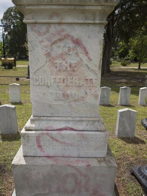 """The vandalized statue, known as """"Silence"""", overlooks a plot of graves reserved for Confederate soldiers in Laurel Grove Cemetery."""