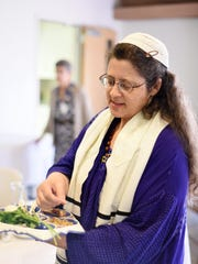 Rabbi Yisraela Tubman explains the items on a Seder plate during a Community Passover Seder on Saturday, April 4, 2015, at Temple Beth Sholom in South Salem. The seder plate traditionally holds five or six items, each of which symbolizes a part of the Passover story.