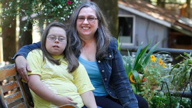 Patie Taylor sits with her special needs daughter, Kimberly, who has Down Syndrome, in August 2012. Taylor hopes the Historic Landmarks Commission on Thursday will approve Salem Hospital's plans to raze historic building Howard Hall and construct an adaptive playground in its place.
