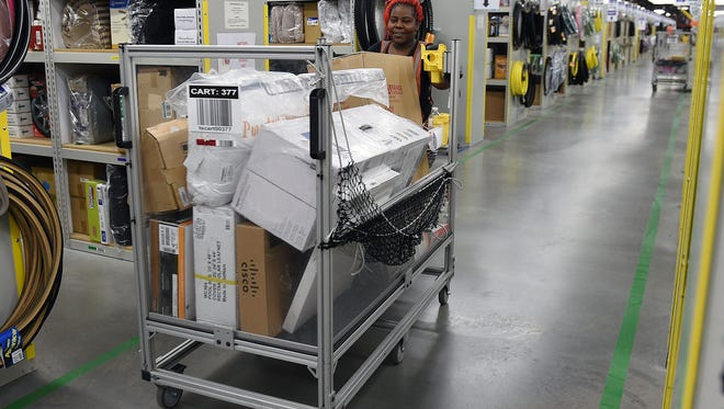 Amazon employee Angela Daniels fulfills customer orders at the Wilson County warehouse in 2015. The e-commerce giant has announced it will hire more than 5,000 corporate employees in Nashville.
