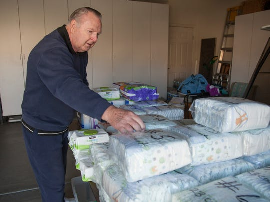 Harvey James collects and distributes donated diapers, and other related items, to local charity organizations from his home in Sun River Saturday, Nov. 28, 2015.