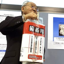 Satoshi Kurosaki, an industry executive who is leading the toilet pear campaign, shows the emergency stock toilet paper at Ministry of Economy, Trade and Industry during an event marking Monday's national disaster prevention day in Tokyo, Monday, Sept. 1, 2014.