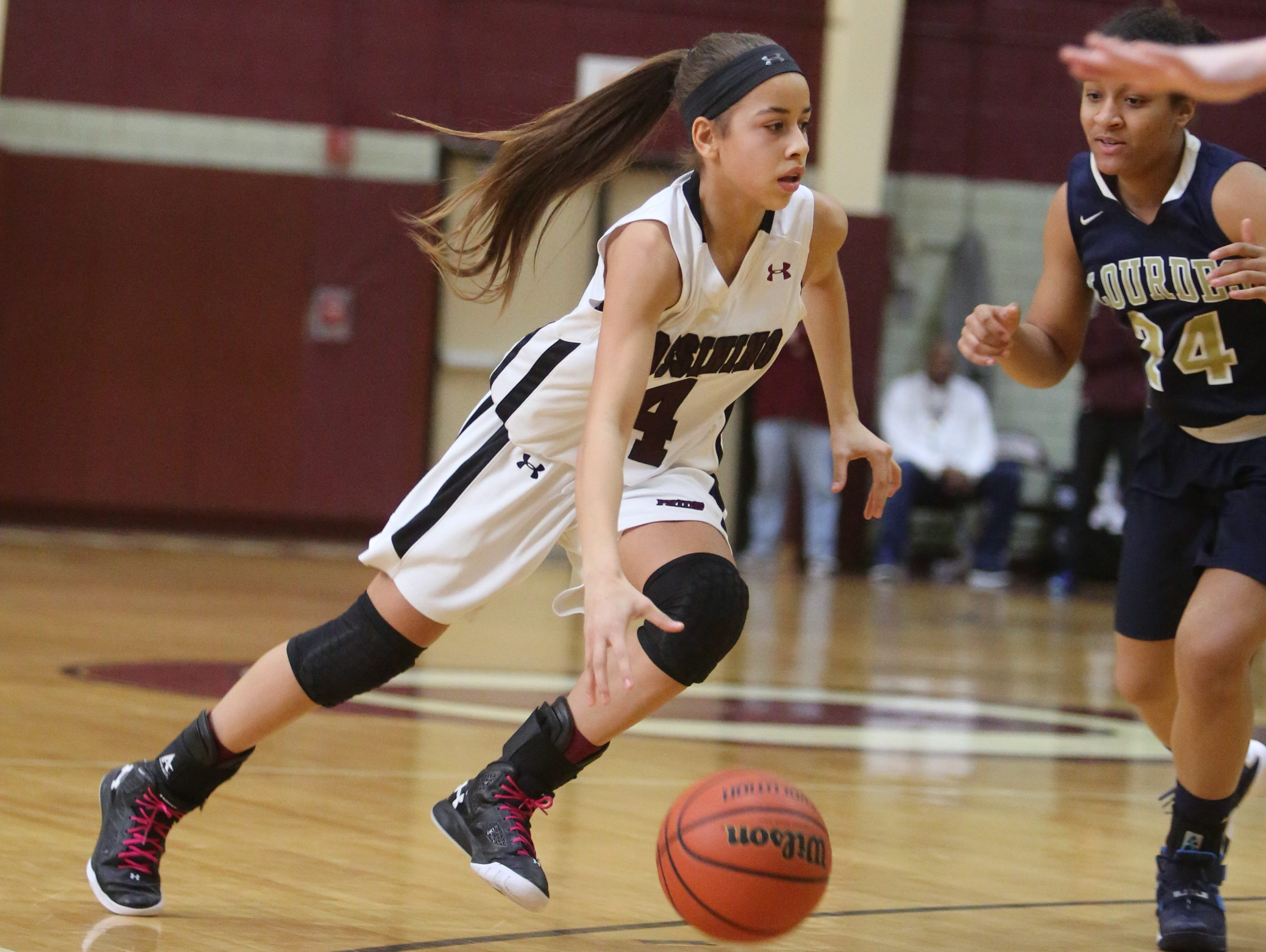 Ossining's Jaida Strippoli move the ball in front of Our Lady of Lourdes' Katie Clarke during their game in Ossining, Feb. 20, 2016. Ossining beat Lourdes, 90-27.