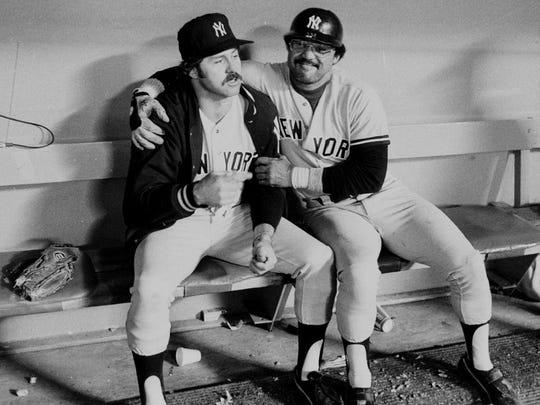 Yankees slugger Reggie Jackson (right) embraces teammate
