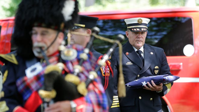 Green Bay Metro Fire Department Fire Chief David Litton holds the memorial flag honoring Hans Hansen, the first Green Bay firefighter to die in the line of duty. The Green Bay Metro Fire Department held a ceremony at Woodlawn Cemetary.